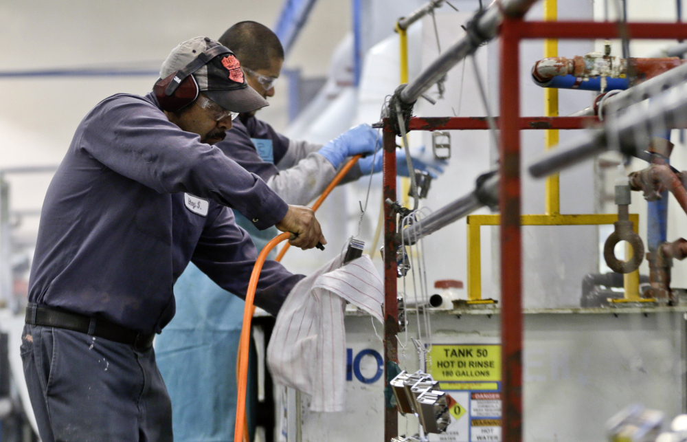 Employees at Sheffield Platers Inc. work on the factory floor in San Diego