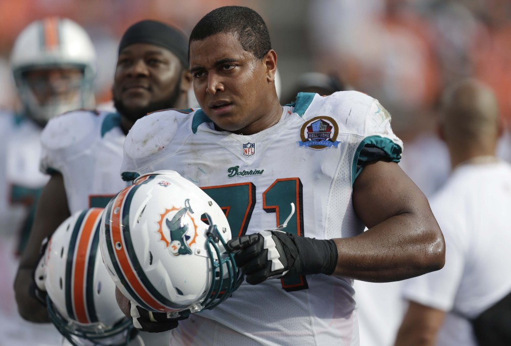 Miami Dolphins tackle Jonathan Martin (71) watches from the sidelines during the second half of an NFL football game against the Jacksonville Jaguars, in Miami, December, 2012.