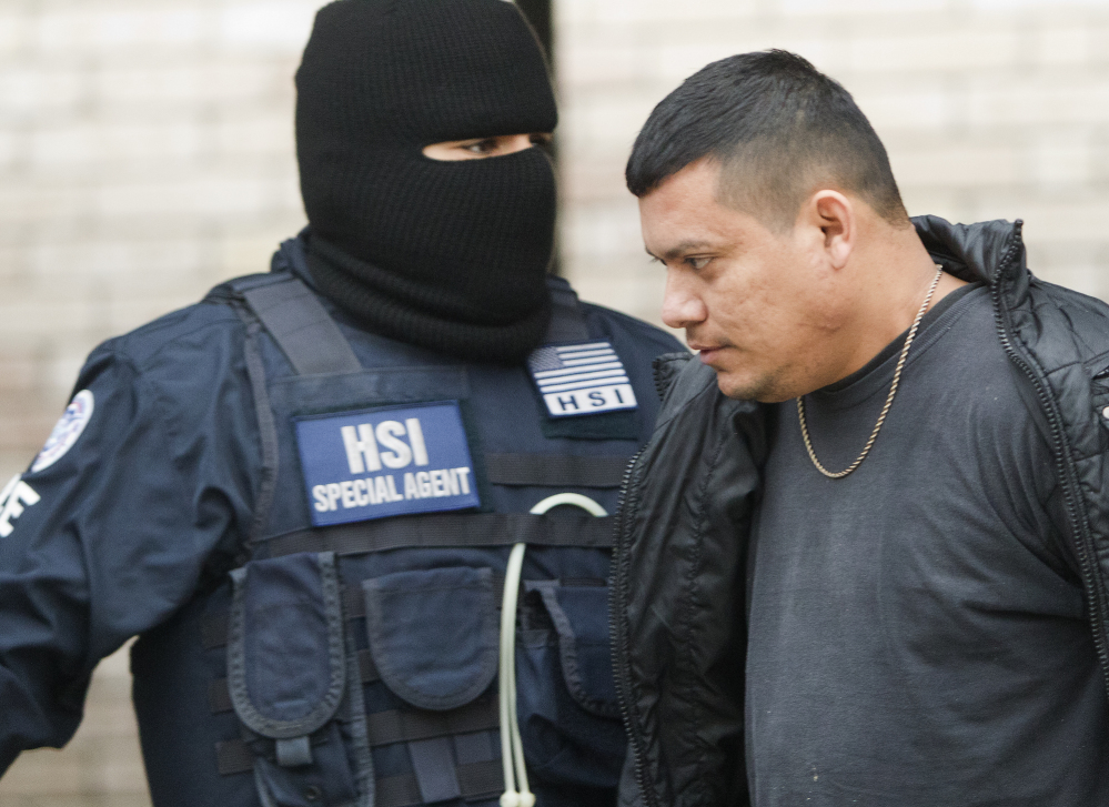 A federal agent escorts an unidentified man after a business was raided, Thursday, Jan. 30, 2014, in southwest Houston.