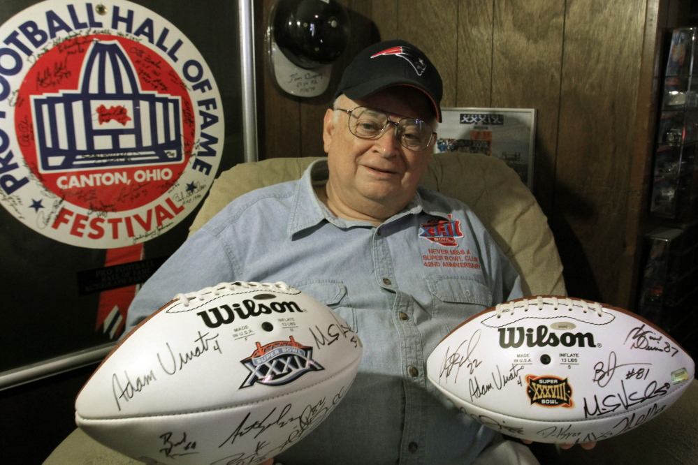 Don Crisman of Kennebunk holds up a few of the footballs he has collected over 44 years of attending all the Super Bowl football games. Crisman is a charter member of the Never Miss a Super Bowl club.
