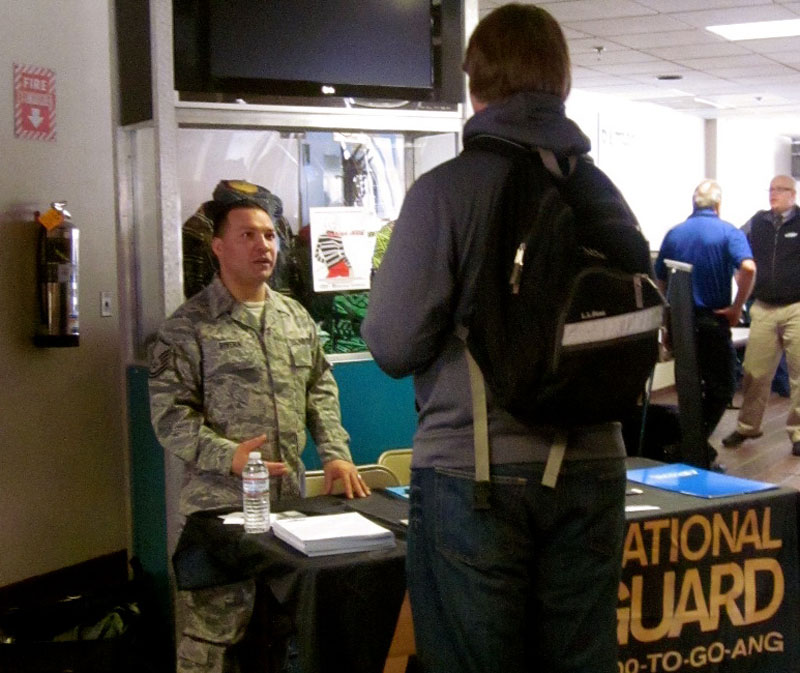 A Maine National Guard recruiter talks to a student at the