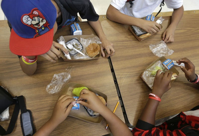 In this Sept. 4, 2013, file photo, students at the Maurice J. Tobin K-8 School in Boston's Roxbury neighborhood eat lunch. The Agriculture Department said Friday, Jan. 3, 2013, it's making permanent rules that allow schools to serve larger portions of lean meat and whole grains in school lunches and other meals.
