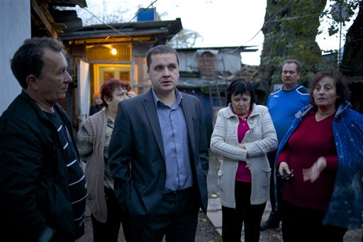 Igor Zarytovsky, center, and his father Vladimir, left, gather with their neighbors in the yard of the railroad house in the village of Vesyoloye outside Sochi, Russia. Unusual for Russia, Sochi area residents are not only willing to talk to reporters but stop them in the street and invite them over to see
