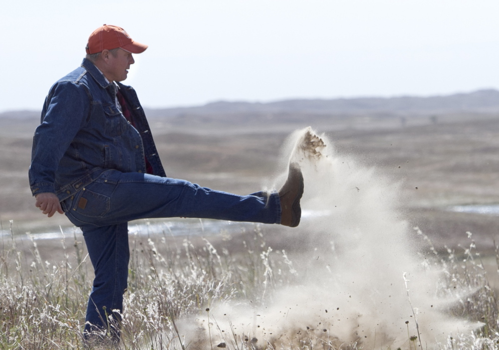 Atkinson, Neb., rancher Bruce Boettcher, who opposes the Keystone XL pipeline, kicks up sand on his land in September 2013 to demonstrate the fragility of the sand hills near the planned route of the pipeline. The long-delayed oil pipeline cleared a major hurdle Friday.