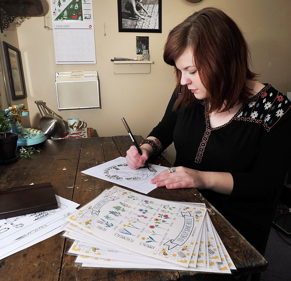 Artist Hannah Rosengren of South Portland works on a drawing in her home studio. In the foreground are several prints of the image featuring herbs, annuals and perennials that she offers for sale on the e-commerce website Etsy.