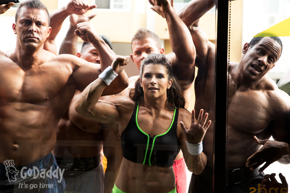 In this image released by GoDaddy.com, NASCAR driver Danica Patrick, center, wearing a muscle suit, appears with bodybuilders in a Super Bowl commercial shot on location in Long Beach, Calif.