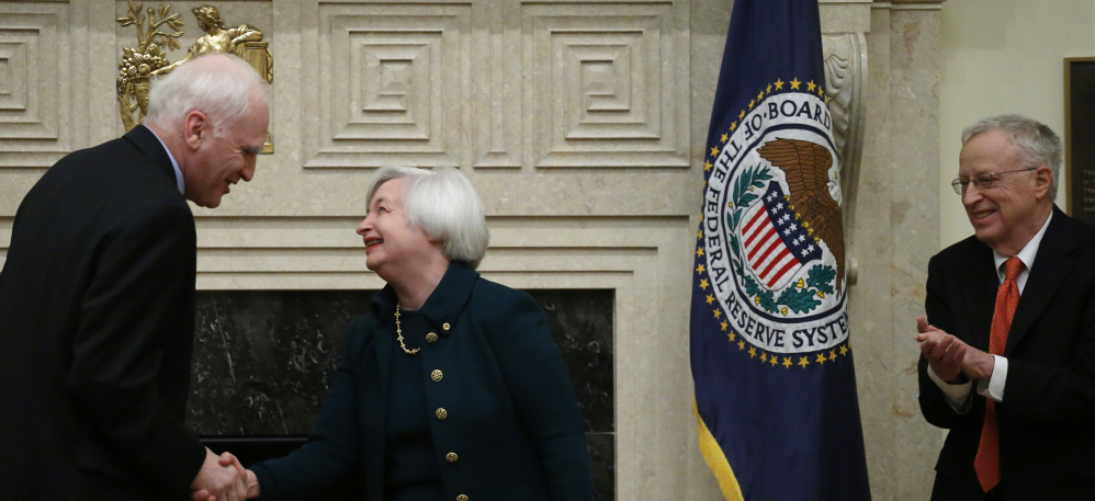 Janet Yellen shakes hands with Daniel K. Tarullo after she was sworn in as Federal Reserve Board chair Monday in Washington. Yellen's husband, Nobel Prize-winning economist George Akerlof, applauds at right.