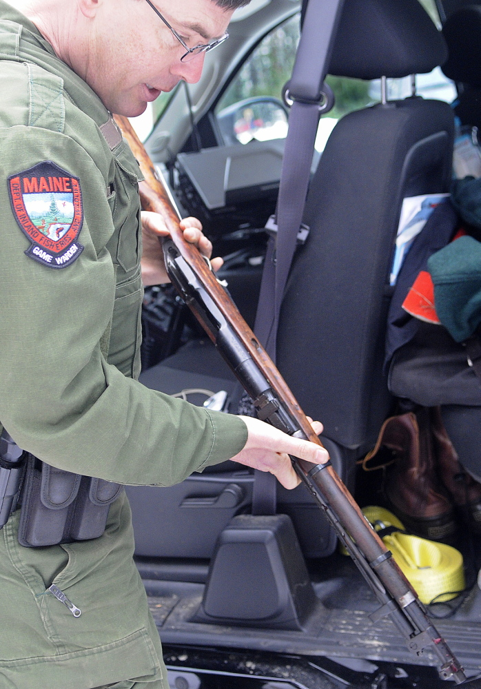 District Game Warden Robert Decker inspects a rifle taken from the scene of a shooting Sunday in West Gardiner after an ice fisherman was hit in the head with a bullet on Cobbosseecontee Stream.
