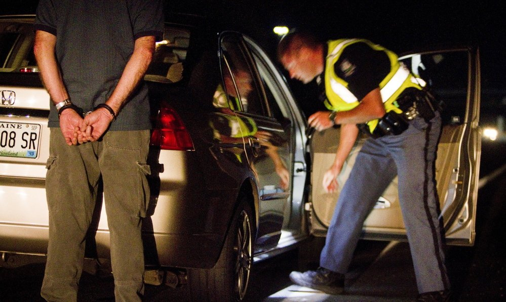 Cumberland police Officer Ryan Martin checks the contents of a vehicle as the driver, suspected of drunken driving, waits behind the car in handcuffs, during a Cumberland County sobriety check in Brunswick in August. A bill under consideration in Augusta would extend the time frame for charging a driver as a repeat offender.