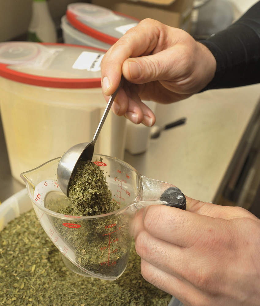 Andrew Menard measures out parsley and other herbs before mixing them with fresh butter to make one of Casco Bay Butter Co.'s specialty blends.