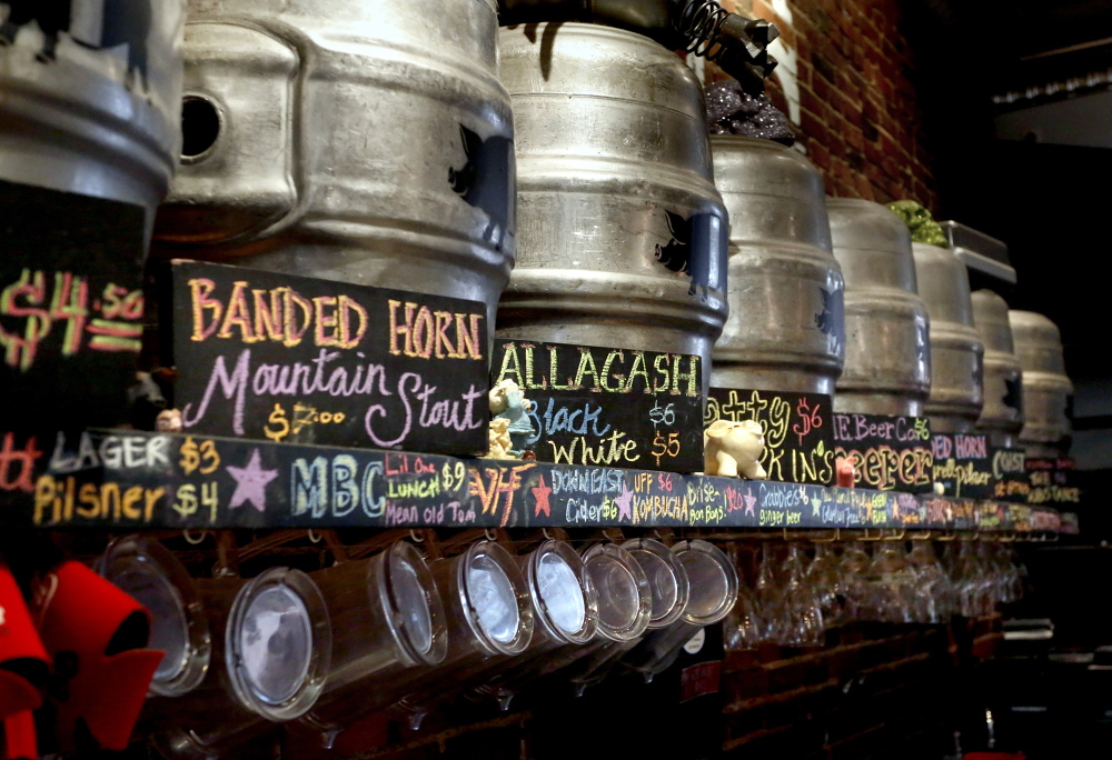 Kegs, the contents of which are described by a sign, line the wall at the The Thirsty Pig in Portland. A 1937 state law prohibits the posting of alcohol content for beers.