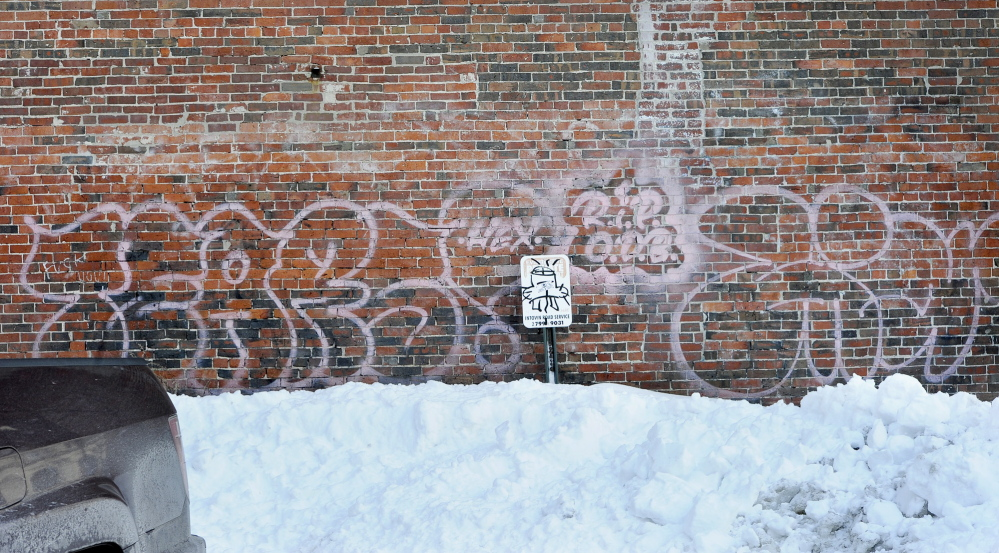 Graffiti marks the side of a building in Monument Square.