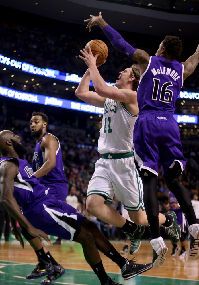 Boston Celtics center Kelly Olynyk (41) drives to the basket against Sacramento Kings shooting guard Ben McLemore (16) and Quincy Acy on Friday in Boston.