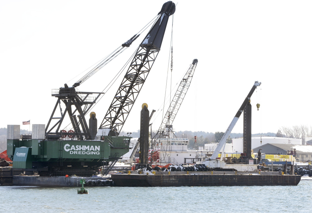 A dredger with a massive crane operated by Cashman Dredging gets ready to begin work upriver from the Casco Bay Bridge on Friday.
