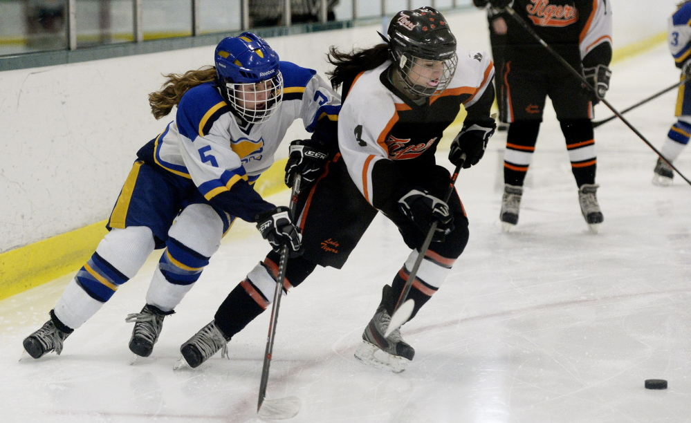 Katherine Dumoulin of Biddeford, right, skates to the puck ahead of Meg Pierce of Falmouth during Falmouth's 5-0 victory Friday night in a West semifinal. The Yachtsmen will meet Cape Elizabeth/Waynflete or Scarborough for the regional title Wednesday night.