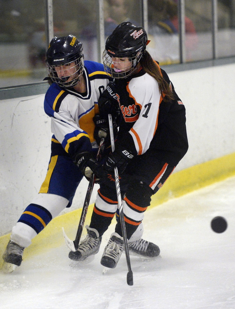 The puck squirts away as Alyse Bazinet of Falmouth, left, and Cassidy Petit of Biddeford battle along the boards during their semifinal at Family Ice Center in Falmouth.