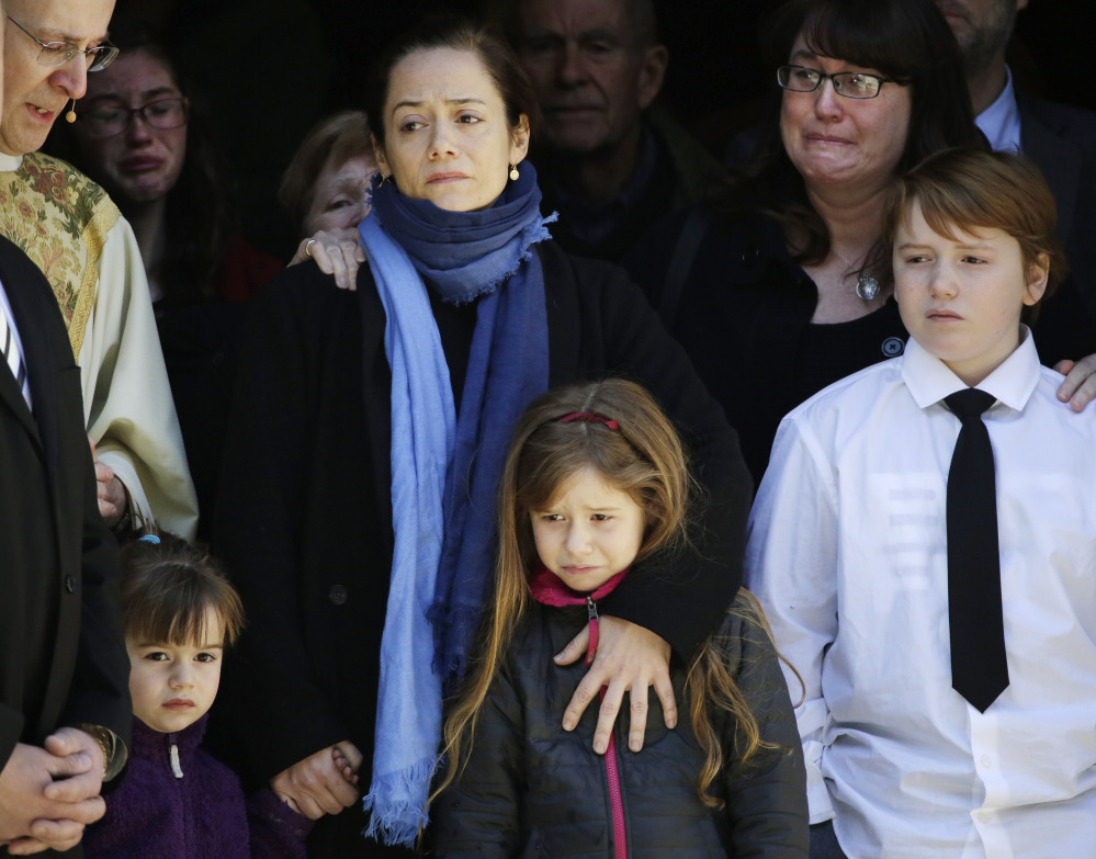 Mimi O'Donnell, center, estranged partner of actor Philip Seymour Hoffman, stands with their three children in the doorway of the Church of St. Ignatius Loyola on Friday.