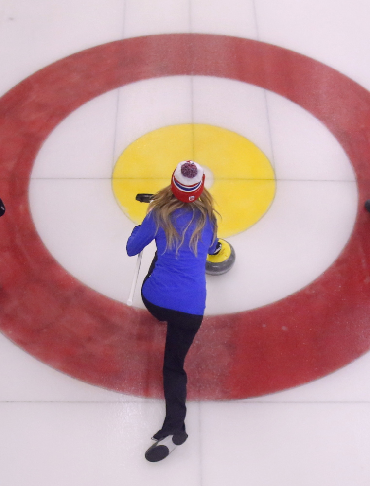 Erin Herbig of Belfast slides through an area known as the house as she throws a curling stone during a competition at the Belfast Curling Club in Belfast on Friday, January 17, 2014.