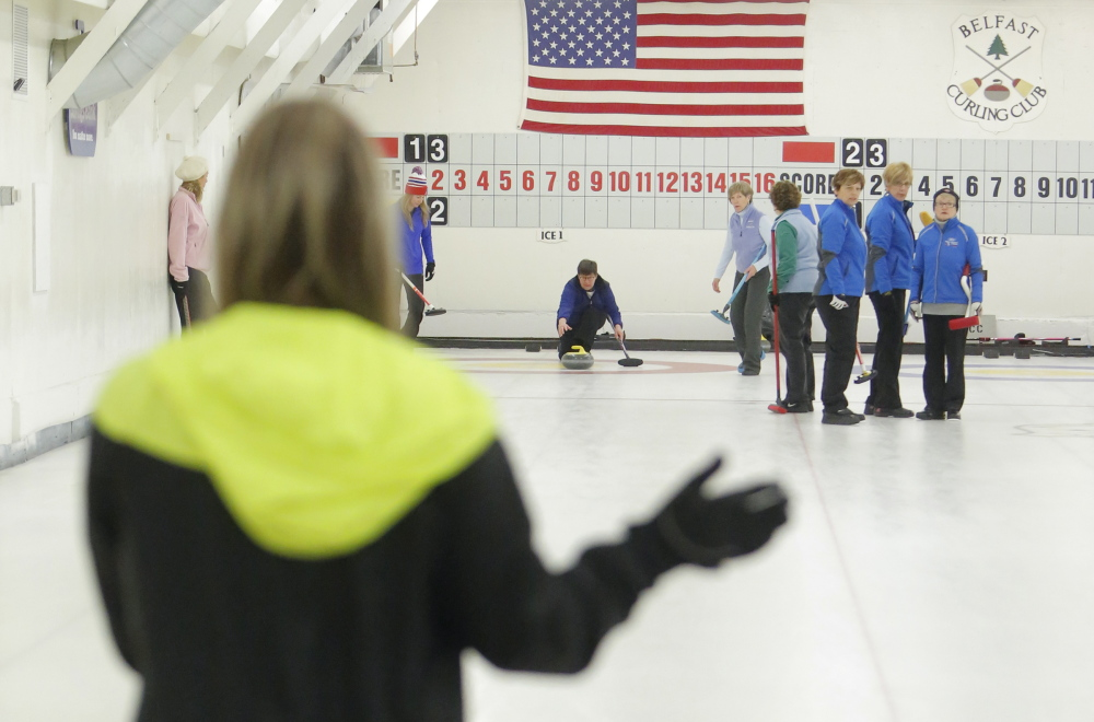 Ann Kirkpatrick of Belmont throws a curling stone under the direction of Erica Sprague, with hand out in foreground, during a curling competition at the Belfast Curling Club in Belfast on Friday, January 17, 2014.