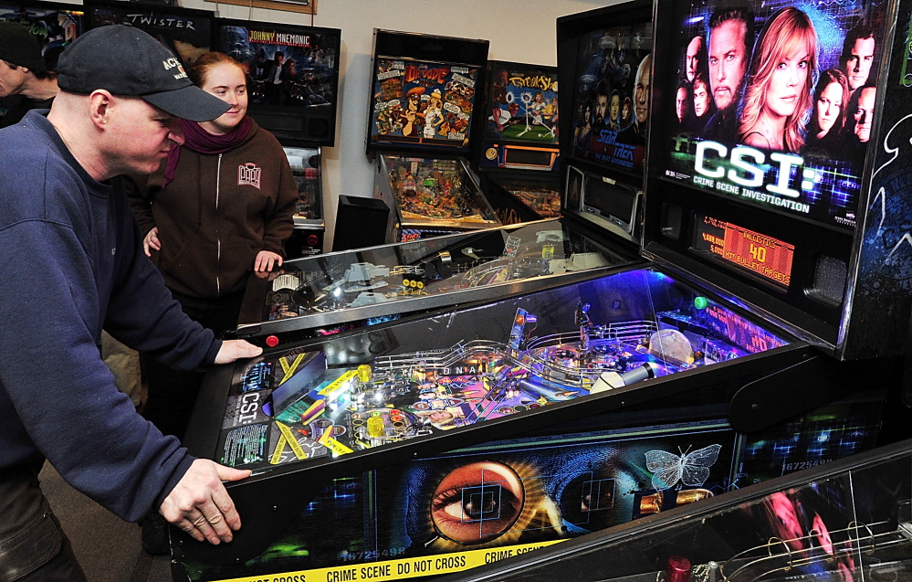 Theresa Nessel of Portland watches as her opponent, Jerry Lindsay of Oakland, racks up the points on CSI, a popular game for the tournament at the Maine State Pinball Championship in Gorham. Saturday, February 8, 2014. Gordon Chibroski, Staff Photographer