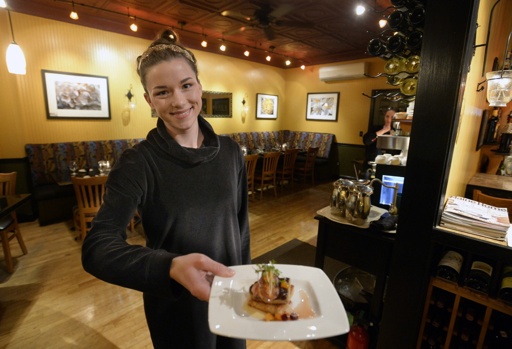 Hostess Hannah Bechard shows off a foie gras medallion and duck breast over buttered toast with apricot conserve and citrus truffle micro greens, finished with duck fat honey, at David's 388.