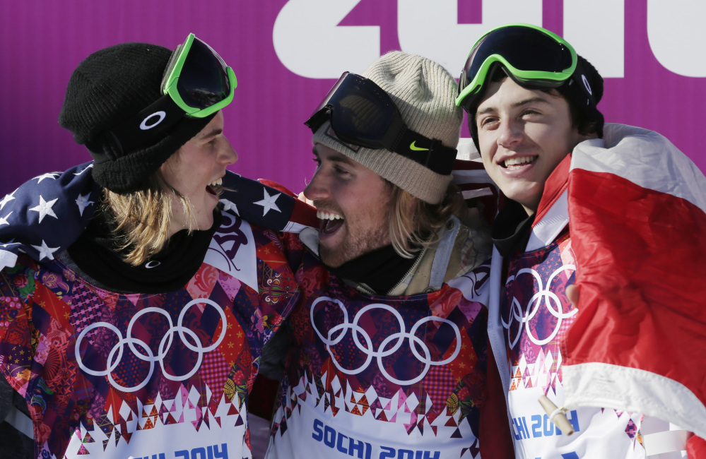 United States' Sage Kotsenburg, center, celebrates with Norway's Staale Sandbech, left, and Canada's Mark McMorris after Kotsenburg won the men's snowboard slopestyle final at the Rosa Khutor Extreme Park. Sandbech took the silver medal and McMorris took bronze.