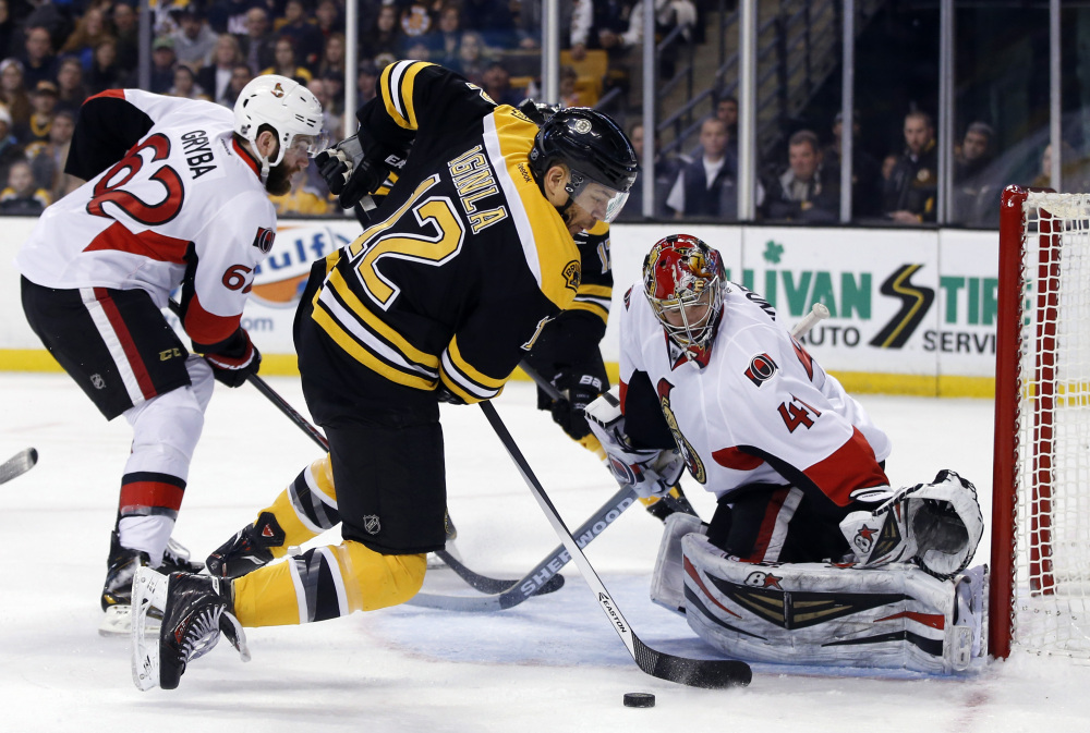 Boston Bruins right wing Jarome Iginla (12) works the puck as Ottawa Senators goalie Craig Anderson (41) and defenseman Eric Gryba (62) protect the goal during the second period of an NHL hockey game in Boston, Saturday.
