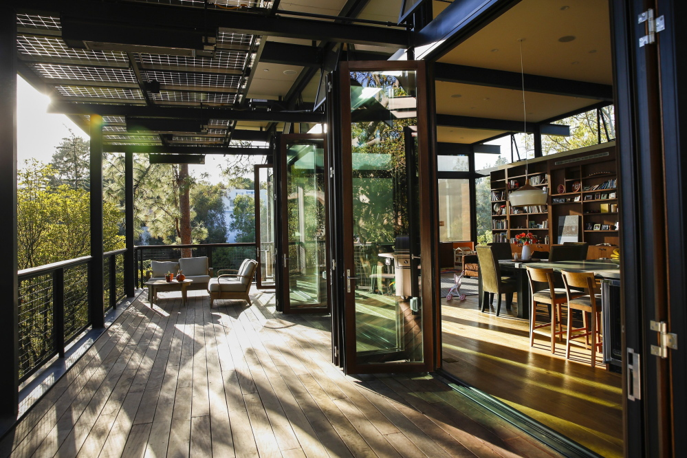 The open floor plan of the main living level flows to a large deck in the Los Angeles home of Janine Poreba and Paul Lieberstein, designed by architect Peter Grueneisen. Overhead solar panels provide shade and electricity for the deck area.