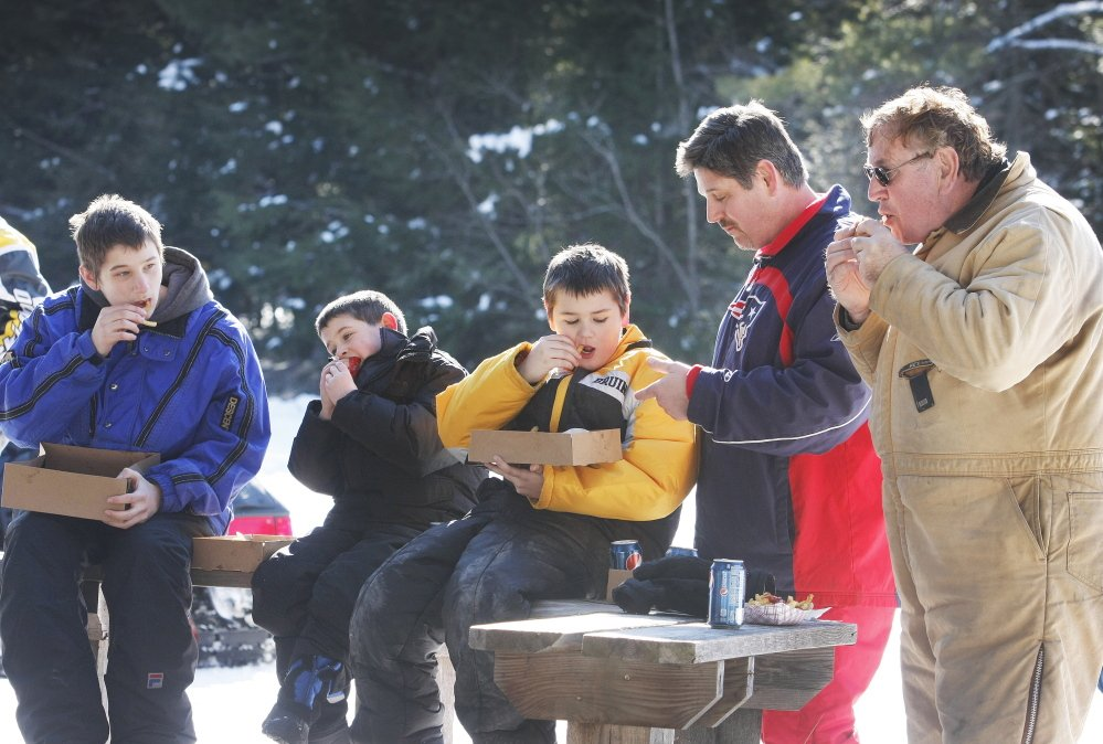 Timothy O'Connor of Buxton, far right, enjoys some lunch with his son, John O'Connor of Rockland, Mass., second from right, and his grandsons, from far left, Timothy, 15, Owen, 7, and John Jr., 11, during a stop at the Sokokis Riders' snack shed and shelter on Route 89 on Sunday.