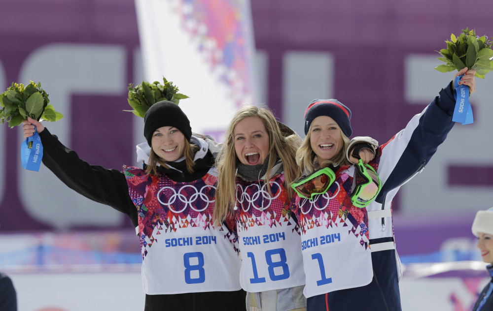 Jamie Anderson of the United States, center, celebrates with silver medalist Enni Rukajarvi of Finland, left, and bronze medalist Jenny Jones of Britain, after Anderson won the women's snowboard slopestyle final at the 2014 Winter Olympics on Sunday.