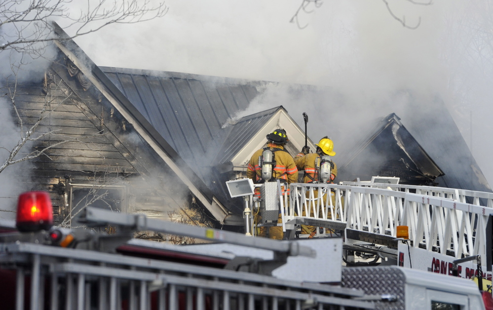 Firefighters use axes from their perches on a ladder truck to access flames while fighting a fire at 16 Weymouth Road in Gray on Monday morning.