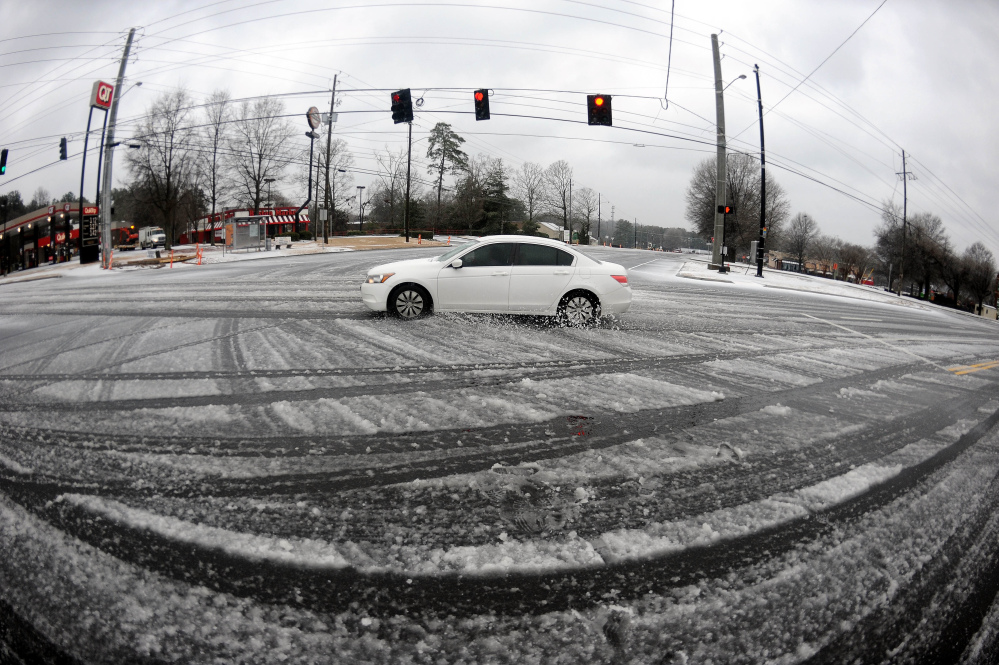 In this photo taken with a fisheye lens, a lone motorist drives through a slick intersection during the morning commute on Wednesday in Atlanta.