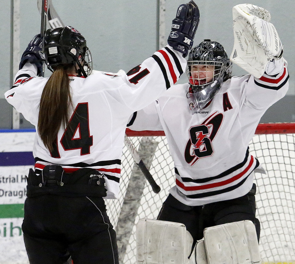 Brenna Kent, left, skates in to celebrate with goalie Devan Kane after Scarborough defeated Falmouth 7-0 in the Western Maine girls' hockey final Wednesday night at the Portland Ice Arena.
