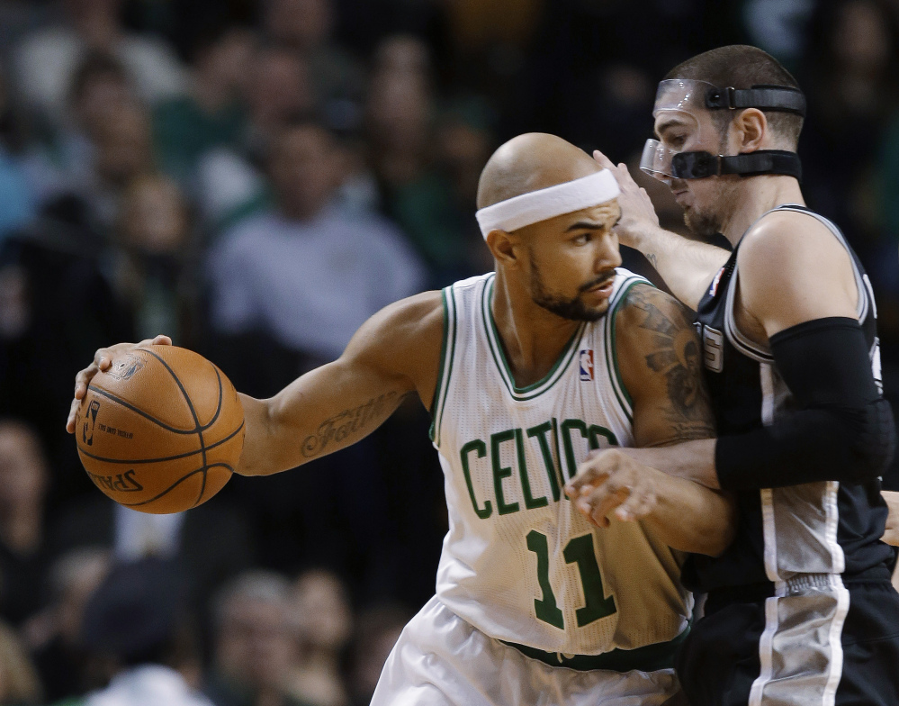 Boston Celtics guard Jerryd Bayless attempts to drive around San Antonio Spurs point guard Nando de Colo during the first half of the game in Boston on Wednesday.