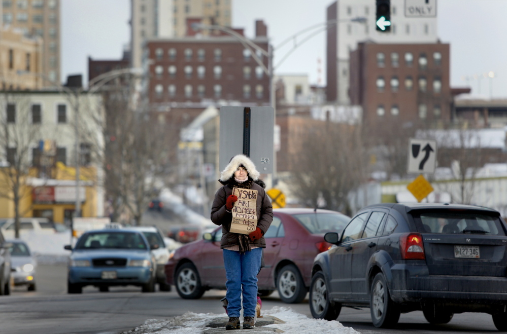 "Laurel Merchant panhandles Wednesday in the median at Preble Street Extension and Marginal Way. Merchant said she was glad to hear the city's ban had been struck down. ""It's my right to be out here,"" she said."