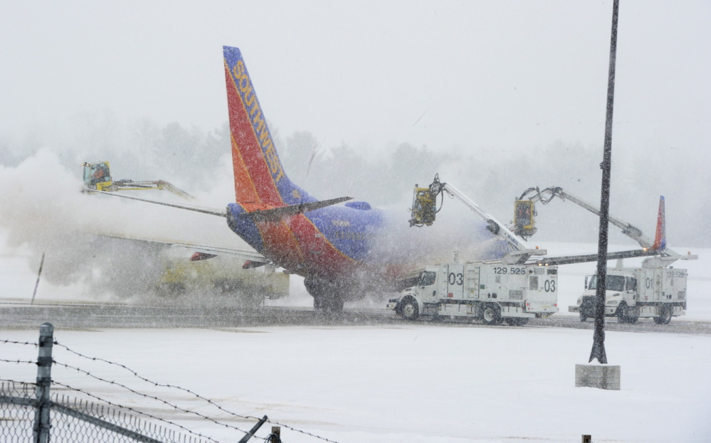 A Portland International Jetport crew de-ices a Southwest jet that was an hour late for its scheduled 11:30 a.m. departure. The flight had already been diverted from Baltimore to Atlanta before its arrival at the jetport early Thursday.