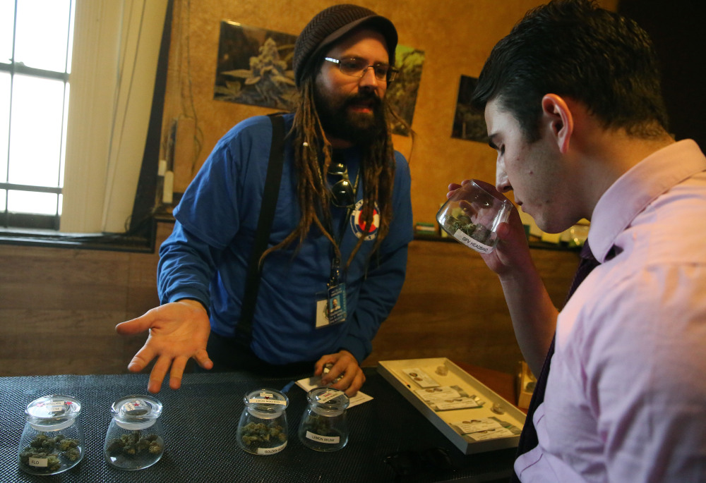 Customer Paxton Berlanga, of Indiana, right, smells a strain of marijuana, while being helped by employee Billy Archilla, inside the retail marijuana shop at 3D Cannabis Center, in Denver, Friday.