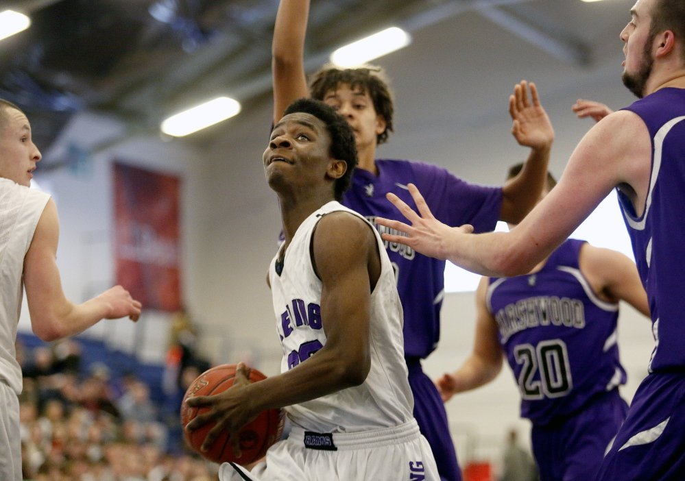 Deering's Ben Williams cuts through a swarm of Marshwood defenders while driving to the basket during a Western Class A boys' basketball quarterfinal Friday at the Portland Expo. Williams scored six of his 20 points in overtime as Deering rallied for a 60-53 victory.