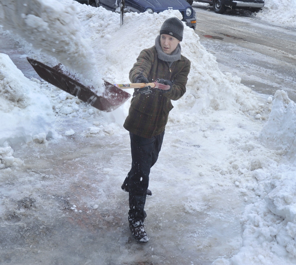 Levi Bridges heaves heavy,wet snow onto banks above his head Friday while clearing his driveway on Portland's Vesper Street. Another storm Saturday could drop another half-foot.