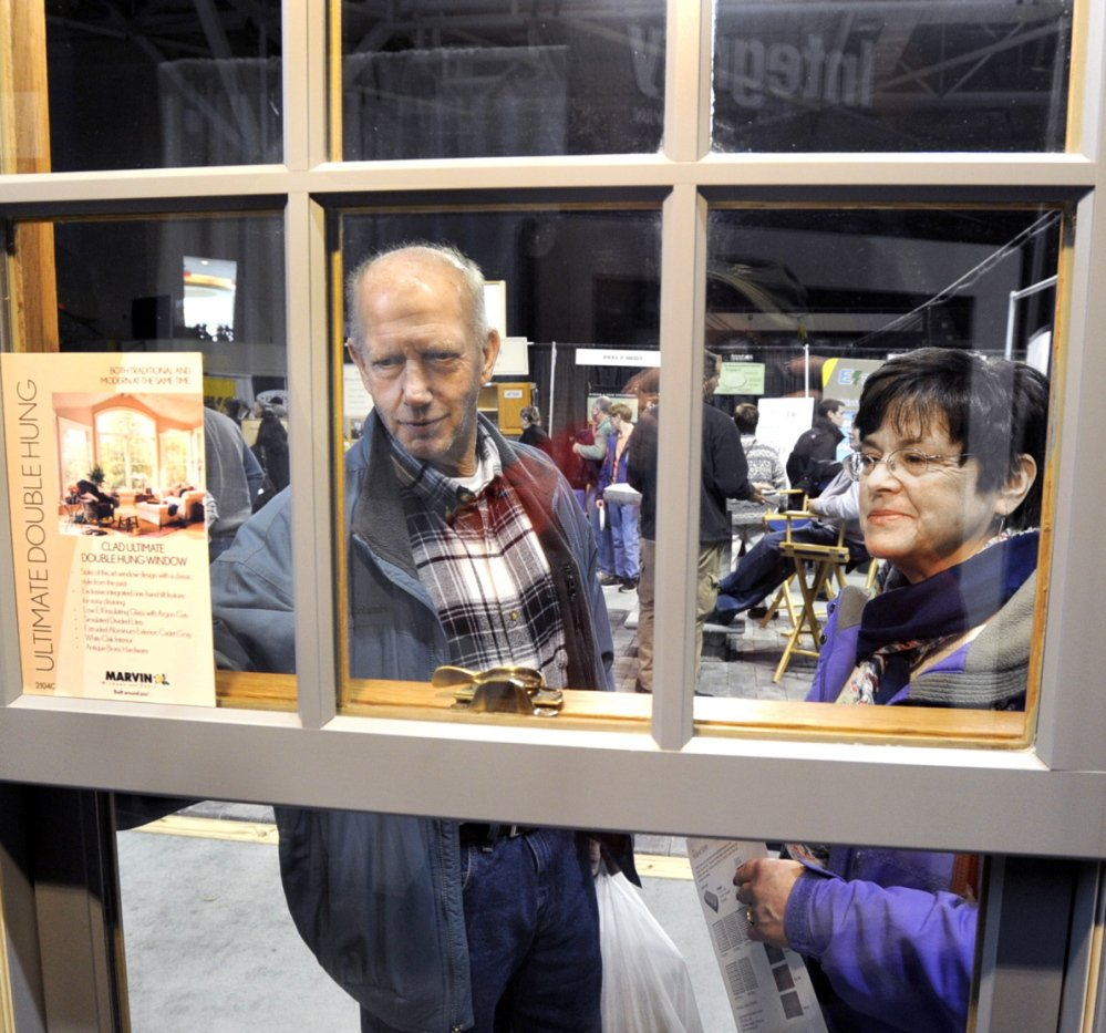 """Wayne and Debra Cilley of Waterboro shop for new windows during the Maine Home, Remodeling and Garden Show at the Cumberland County Civic Center in Portland on Saturday. """"We are gathering information and hope to be able to gather some estimates,"""" she said."""