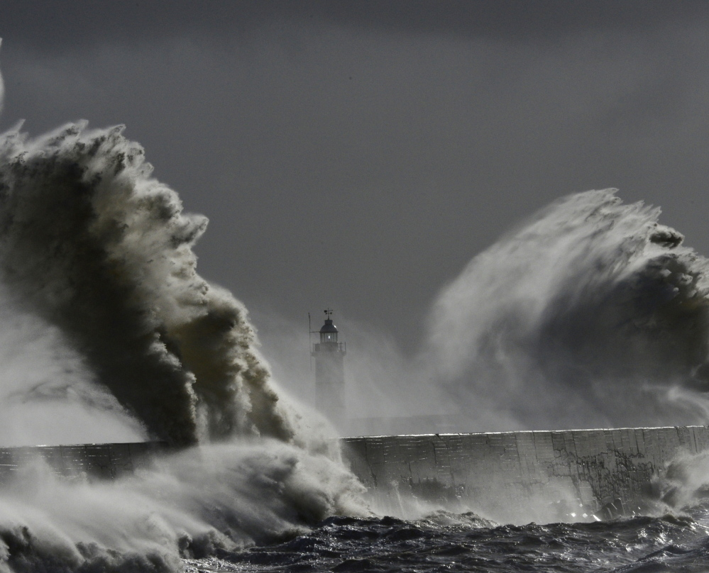 Large waves hit the lighthouse and harbor during high tide Saturday at Newhaven in Sussex, southern England.