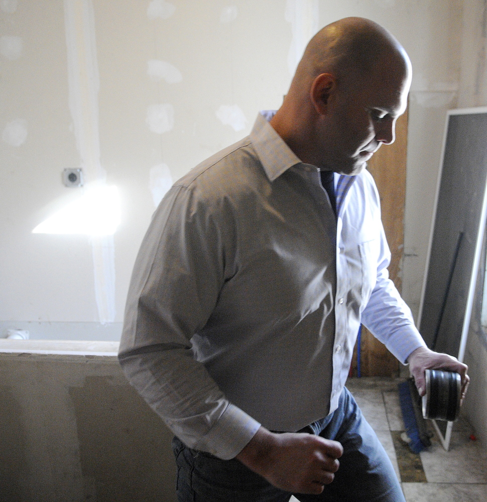 Jason Mills of Maine Professional Inspections collects a radon test at an apartment building in Augusta.