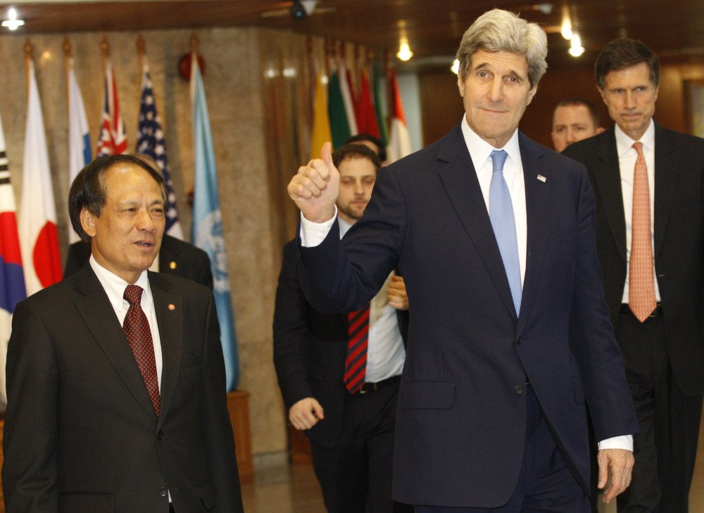 U.S. Secretary of State John Kerry, right, waves to the press after meeting with Secretary-General of Association of Southeast Asian Nations (ASEAN), Le Luong Minh , left, at the ASEAN headquarters in Jakarta, Indonesia on Sunday.