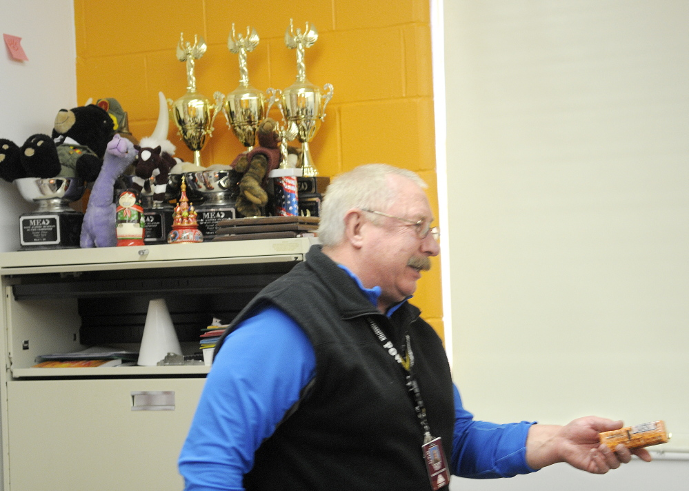 Retired teacher and Academic Decathlon coach Scott Foyt hands out crackers to Monmouth Academy's Academic Decathon team during a recent practice. Foyt and his wife, Cathy, have coached the school's team for several years at the Monmouth school.