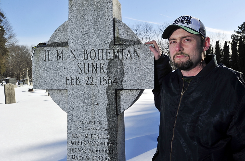 """Historian Matthew Jude Barker stands with the Celtic cross honoring victims of the RMS Bohemian shipwreck – """"HMS"""" was an error, he said – in South Portland's Calvary Cemetery."""
