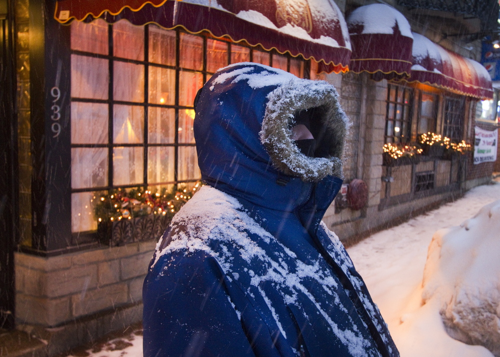 """Bundled in the appropriate gear, Darin Berrick of Portland stands in front of The Inn at St. John on Congress Street in Portland during heavy snowfall Tuesday evening. """"I wish it would go away. It's definitely getting old,"""" said Berrick."""
