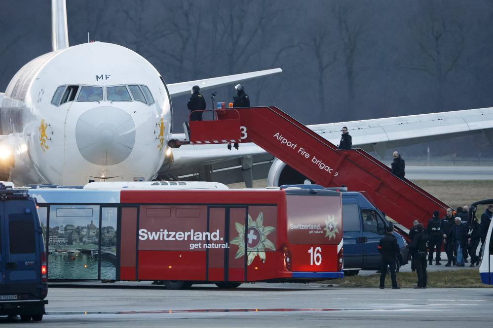 """Police board a hijacked Ethiopian Airlines plane in Geneva, Switzerland, Monday. After he was arrested by Swiss authorities, the pilot said he felt """"threatened"""" in Ethiopia, police said but did not specify why or by whom he claimed to feel threatened."""