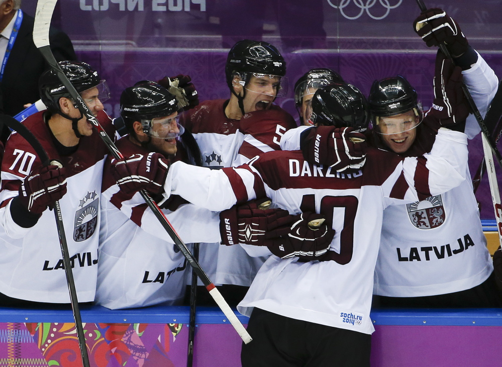 Latvia forward Lauris Darzins is congratulated by teammates after scoring against Switzerland in the third period of a men's ice hockey game at the 2014 Winter Olympics on Tuesday in Sochi, Russia. Latvia won 3-1 to advance to the quarterfinals.