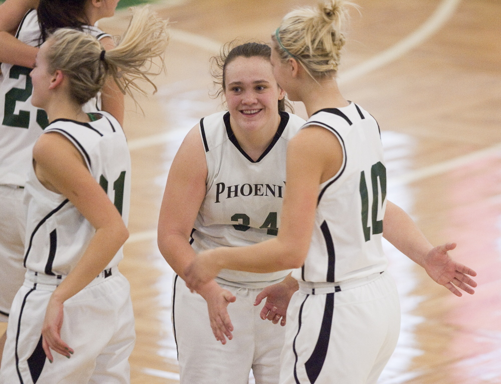 Spruce Mountain's Emily Keene, center, celebrates with teammate Victoria Ouellette after their team beat Fryeburg Academy 55-51 in a Western Class B girls' basketball quarterfinal Wednesday at the Portland Expo.
