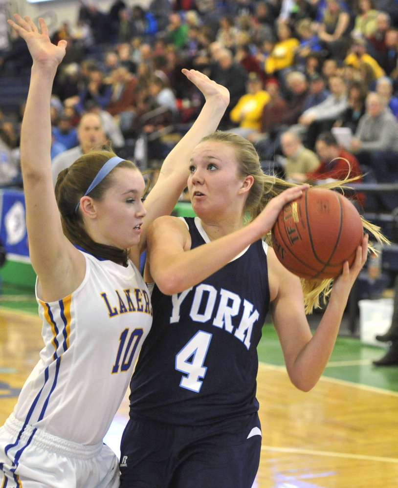 York's Shannon Todd tries to drive to the basket against Jordan Turner of Lake Region during their Western Class B girls' basketball quarterfinal Wednesday at the Portland Expo. Lake Region, the two-time defending regional champion, advanced with a 58-42 win.